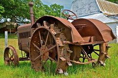 Antique Rusty Tractor in Field. An antiquated rusty tractor with steel lugs in the wheels resides behind an old farm barn Royalty Free Stock Photos