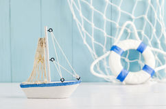 Antique sail boat Toy model with rope and seashell - Nautical ba. Antique sail boat Toy model with rope and seashell on white and blue wooden background Stock Images