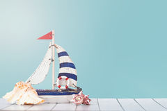 Antique sail boat Toy model with Ship`wheel, rope and seashell on white and blue wooden background - Nautical background. Summer holiday background. Sea card Stock Images
