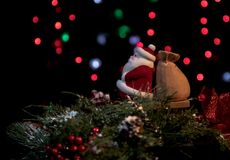 Antique Santa with bag on a Christmas wreath and blurred lights in the background Stock Photos