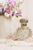 Antique Scent Bottle. Antique glass scent bottle on ladies dressing table with pearl necklace royalty free stock photography