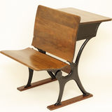 Antique School Chair and Desk. Old wood and metal combination school chair in front and school desk in back royalty free stock images