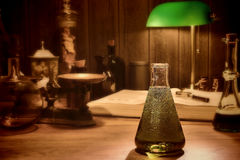 Antique Science and Chemistry Research Laboratory. With an old conical glass lab Erlenmeyer flask filled with potion and vintage scientific instruments in retro stock image