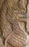 Antique sculpture of dragon on wood. Grunge antique sculpture of dragon on wood Royalty Free Stock Photo
