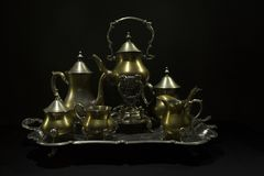 Antique service. Antiques on an old silver tray on a dark backgr stock image