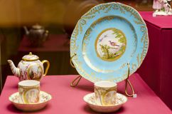 An antique set of ceramic teapots, cups, saucers on a wooden table. Stock Image