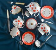 Antique set of dishes on a dark colored cloth tablecloth. Ceramic teapot, saucer, cup. Top view. Antique set of dishes on a dark cloth tablecloth. Ceramic teapot Royalty Free Stock Image
