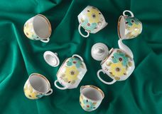 Antique set of dishes on a dark colored cloth tablecloth. Ceramic teapot, saucer, cup. Top view.  Stock Image