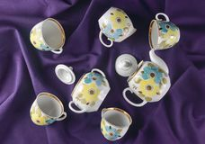Antique set of dishes on a dark colored cloth tablecloth. Ceramic teapot, saucer, cup. Top view.  Royalty Free Stock Images