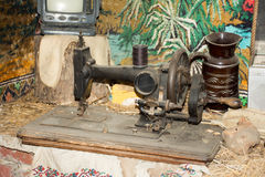 Antique sewing machine. An old sewing machine, standing on a special table, some ornaments royalty free stock photos