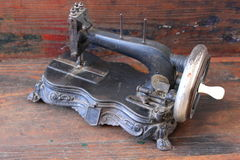 Antique sewing machine. On old wooden sofa Royalty Free Stock Image