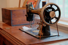 Antique Sewing Machine. Antique treadle sewing machine on a bench with loaded thread spool Stock Images