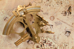 Antique sextant on old map. A sextant is an instrument used to measure the angle between any two visible objects. Its primary use is to determine the angle Royalty Free Stock Images