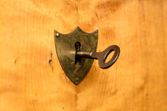 Antique shield-shaped lock on bright cherry wood, focus on the lock. Antique shield-shaped lock on bright cherry wood, side view, focus on the lock, copy space Stock Images