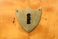 Antique shield-shaped lock on bright cherry wood. Frontal view Stock Images