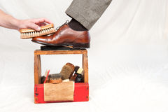 Antique shoe shine box. A man gets his shoes polished by a worker using a vintage shoe shine box with camel hair brushes, polishing rag, polish and a wooden shoe Royalty Free Stock Images