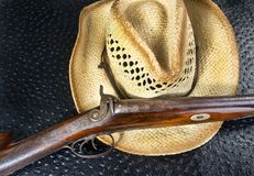 Antique Shotgun and Straw Hat. Royalty Free Stock Photos
