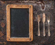 Antique silver cutlery and blackboard for your text. Retro style Royalty Free Stock Image