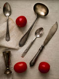 Antique silver cutlery and cherry tomatoes on canvas, top view Royalty Free Stock Photos