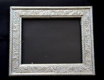 Antique silver frame. (dirty glass pane in centre) with ornamental decoration on black background stock images