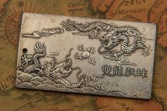 Antique silver plate with fighting dragons On Ancient oriental-style World Map royalty free stock image