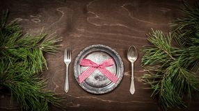 Antique silver plate, spoon, fork and pine branches on a dark wooden background stock image
