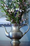 Antique silver teapot with spring arrangement Royalty Free Stock Photos