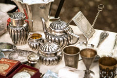 Antique silver teapots, creamer and other utensils at a flea market. Old metal tableware collectibles at a garage sale stock photography