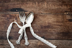 Antique Silverware over a Rough Wooden Background. Antique silverware spoon and fork tied with lace ribbon over a rustic old wooden background with a grunge like Stock Photos