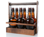 Antique Six Pack Beer Carrier. Closeup of an antique wooden six pack beer carrier with swing top beer bottles on a white background with reflection Stock Photo
