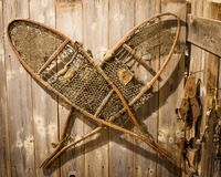 Antique Snow Shoes Hanging on Wooden Wall stock images
