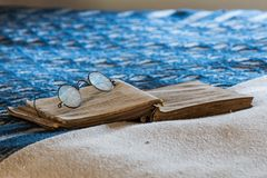 Antique Spectacles on Book on Bed Stock Photo