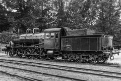 Old steam locomotive standing on some old railroad track. Antique steam locomotive in black and white, standing at an old train station in Sweden Royalty Free Stock Image