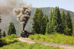 An antique steam train in colorado. A coal-fed train carrying passengers on a scheduled trip through the mountains Royalty Free Stock Photo