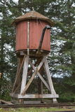 Antique steam train water tower. With trees in the background royalty free stock photo
