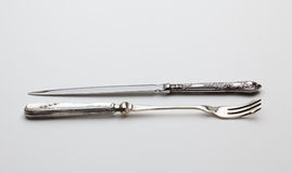 Antique sterling silver knive and fork. Old fashioned sterling silver objects being a decorated knive and fork used for cakes Royalty Free Stock Images