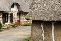Antique stone Brittany houses in France. Traditional stone homes with shutters and thatched roofs in Brittany, on west coast of France Royalty Free Stock Photo