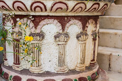 Antique stone floor flowerpot in Greek or Roman style with pillar ornament. White and red colors, yellow flowers, Spain Stock Photo