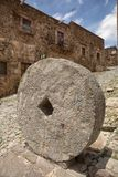 Antique stone mill wheel on the street Stock Photography