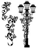 Antique street light among roses Royalty Free Stock Photos