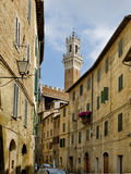 Antique street of Sinea with Mangia tower in background. Siena, Italy Royalty Free Stock Photography