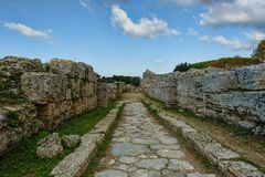 Antique street under blue skies with fluffy white clouds in an a. Ncient city ruins, Paestum, Campania, Italy Stock Photos