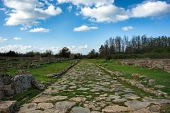 Antique street under blue skies with fluffy white clouds in an a. Ncient city ruins, Paestum, Campania, Italy Stock Image