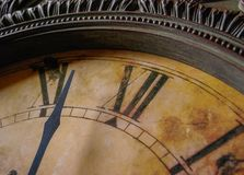 An antique-style analog clock nears the 12 o'clock hour. An antique-style analog clock, with a burnt yellow finish, nears the 12 o`clock hour stock photography