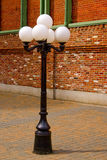 Antique Style Street Lamp in front of Brick Wall. An old-fashioned metal street lamp surrounded by red brick royalty free stock image