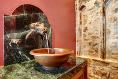 Antique style washbasin cabinet with a dragon head. Beautiful antique washbasin cabinet with a stoned dragon head, vessel sink and green marble counter top Royalty Free Stock Photo