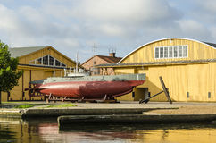 Antique submarine HMS Hajen. Swedens first submarine HMS Hajen (English: The Shark) standing in front of the hangars of Karlskrona flight station built in the Stock Photos