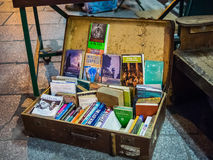 Antique suitcase serves as book display space on sidewalk outsid. E Shakespeare and Company bookstore, paris, France. Detail of worn wooden bench visible at Stock Image