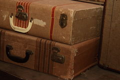 Antique Suitcases In A Pile. Antique brown tattered suitcases with faded red stripes stacked in a museum display and photographed close-up Royalty Free Stock Photography