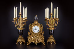 Antique table clock and two candlesticks with candles Stock Photos